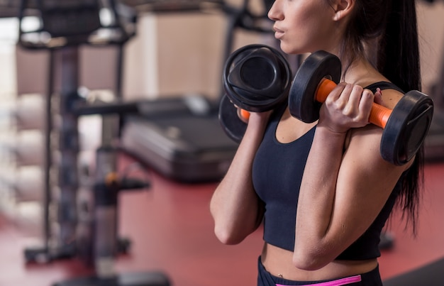 Allenamento corpo e mente nello studio fitness loft. primo piano sulla donna di forma fisica che prende testa di legno dal pavimento nella palestra urbana del sottotetto