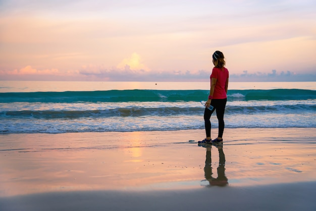 Allenamento corrente della ragazza che pareggia sulla spiaggia di mattina.