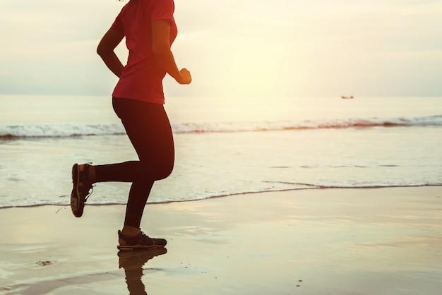 Allenamento da jogging donna sulla spiaggia al mattino