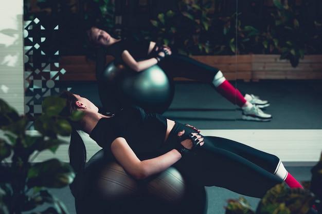 Allenamento della donna con palla ginnastica in palestra