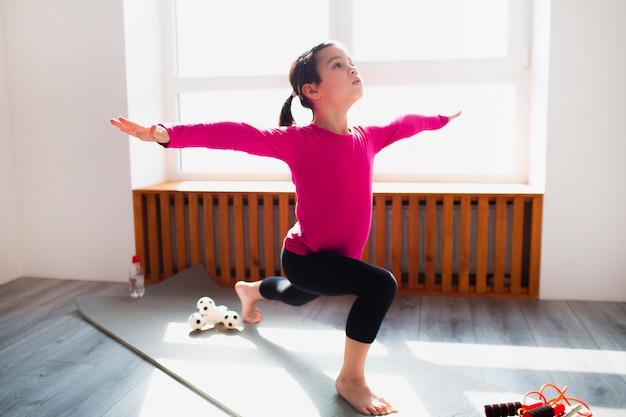 Allenamento di affondo di andata della bambina a casa. ragazzo carino si sta allenando su una stuoia al coperto. la piccola modella mora in abiti sportivi ha esercizi vicino alla finestra nella sua stanza