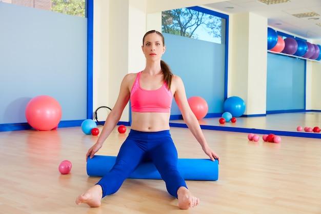 Allenamento di esercizio del rullo della donna di pilates alla palestra