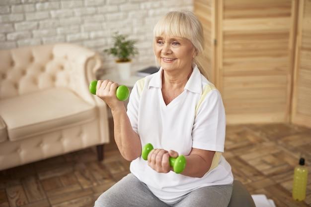 Allenamento di esercizio di manubri bicipiti su palla fitness.