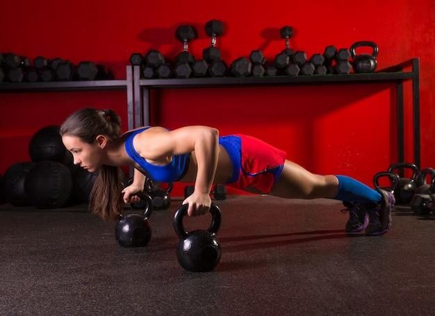 Allenamento di palestra di forza di donna push-up kettlebells