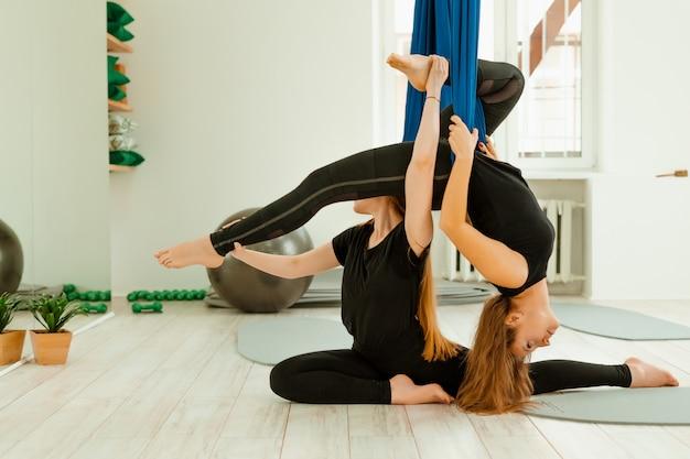 Allenamento di stretching. un gruppo di ragazze in uniforme nera sta facendo un allenamento di stretching in palestra. akroyoga, yoga, fitness, allenamento.