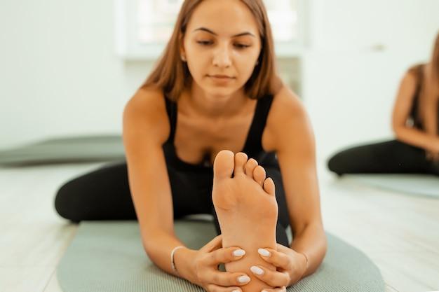 Allenamento di stretching. uno stile di vita sano. la giovane bella donna in uniforme nera sta facendo allungando l'esercizio. akroyoga, yoga, fitness, allenamento, sport.