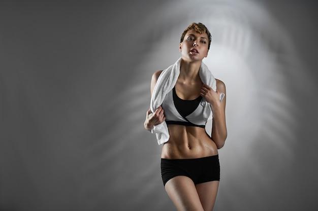 Allenamento fatto. ritratto dello studio di giovane posa della donna di forma fisica