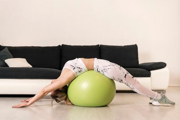 Allenamento femminile ad alto angolo con palla fitness