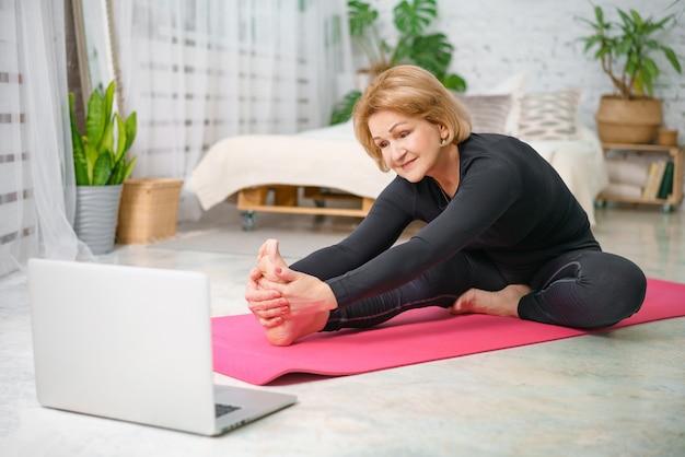 Allenamento fitness online, donna senior a casa con il computer portatile.