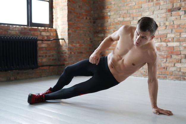 Allenamento fitness uomo. uomo senza camicia che fa allungando a casa