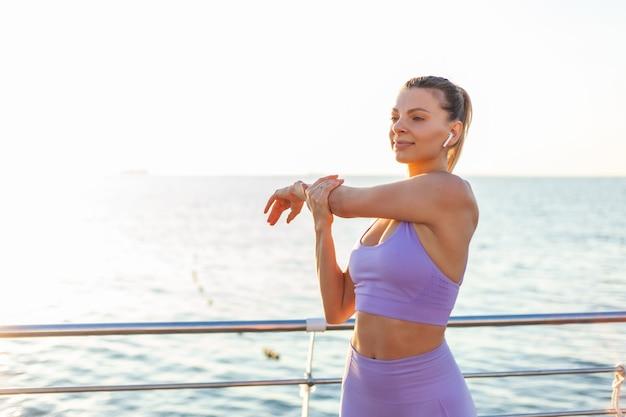 Allenamento mattutino. riscaldamento prima dell'allenamento. donna adatta dei giovani in abiti sportivi che fanno mano che allunga sulla spiaggia all'alba