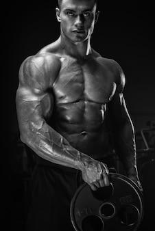 Allenamento muscolare dell'uomo con il piatto del bilanciere