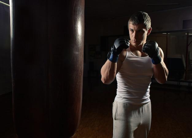 Allenamento pugile giovane uomo muscoloso con sacco da boxe in interni scuri