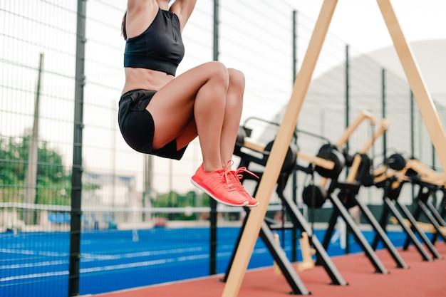 Allenamento sportivo in forma della donna e allenamento sullo stadio al mattino