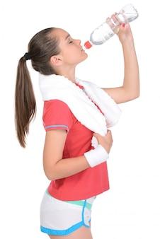 Allenamento teenager di forma fisica della ragazza, tenente asciugamano ed acqua.