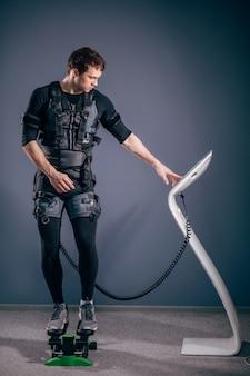 Allenamento uomo su stepper con stimolazione muscolare elettrica