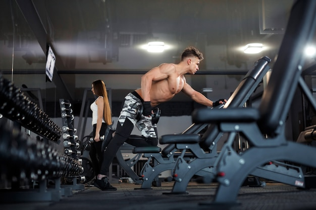 Allenarsi nel centro fitness uomini e ragazze