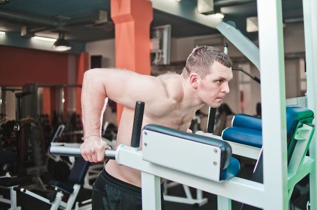 Allenarsi. uomo muscolare che fa i piegamenti sulle barre irregolari nella palestra del crossfit.