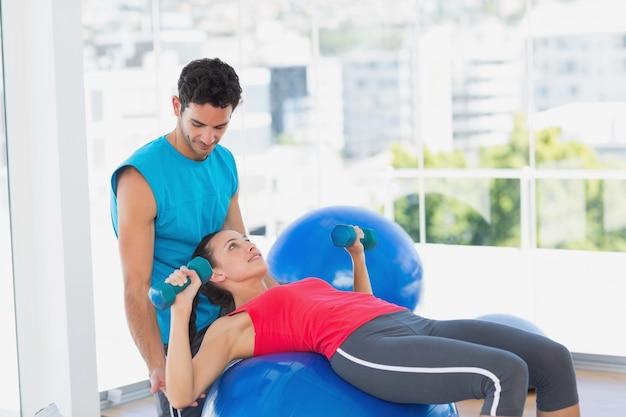 Allenatore aiutando la donna con i suoi esercizi in palestra
