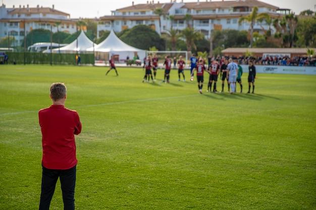 Allenatore di football americano che guarda la sua squadra nella preparazione di una partita di calcio