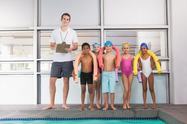 Allenatore di nuoto con i suoi studenti a bordo piscina