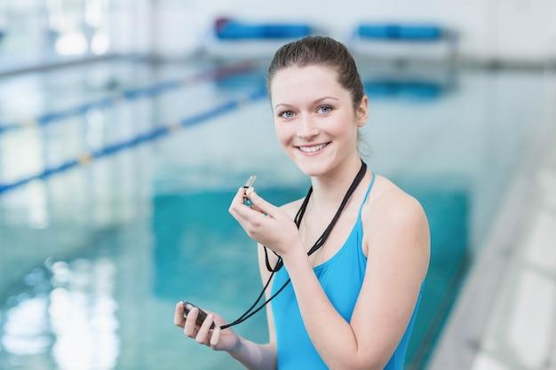 Allenatore grazioso che soffia fischietto e guardando il cronometro in piscina