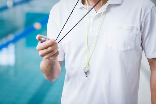 Allenatore in forma guardando il cronometro in piscina