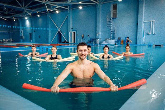 Allenatore maschio e gruppo femminile, allenamento di aerobica in acqua in piscina