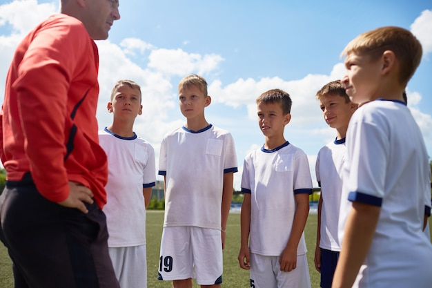 Allenatore motivating junior football team