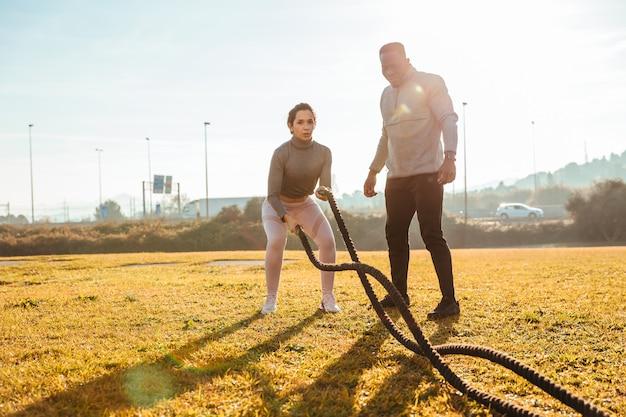 Allenatore personale che allena una ragazza con le corde