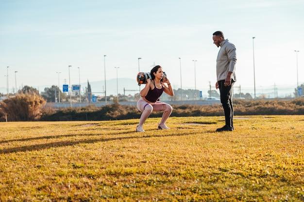 Allenatore personale che allena una ragazza fuori