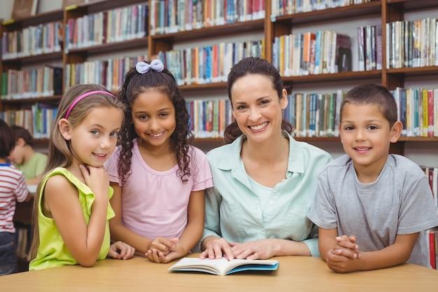 Allievi e libro di lettura dell'insegnante in biblioteca