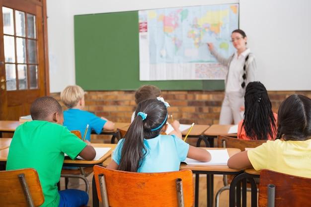 Allievi svegli che scrivono allo scrittorio in aula