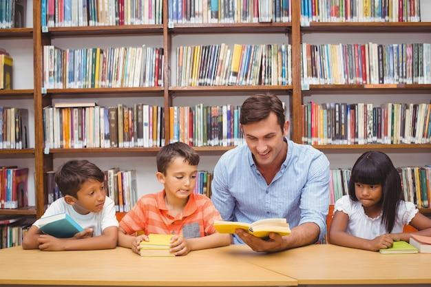 Allievi svegli e insegnante che leggono in biblioteca
