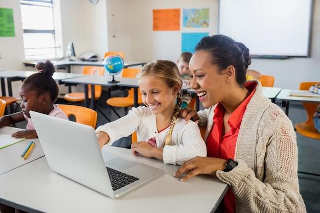 Allievo d'aiuto dell'insegnante con il computer portatile