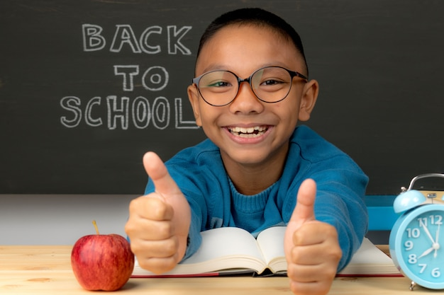 Allievo dalla scuola elementare in occhiali con la mano alzante. il bambino è pronto per imparare. di nuovo a scuola.