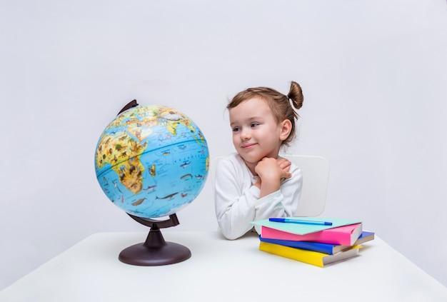 Allievo felice della ragazza con un globo e libri che si siedono al tavolo. la pupilla della bambina in una giacca bianca esamina un globo su un bianco isolato