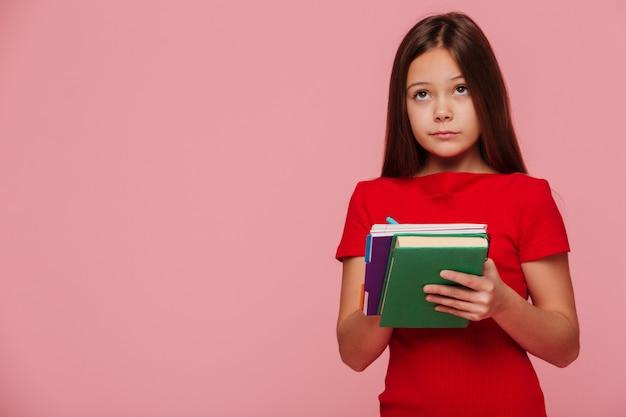 Allievo pensieroso della ragazza che esamina lo spazio della copia e che tiene i libri