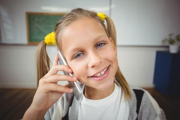 Allievo sorridente che telefona con lo smartphone in un'aula