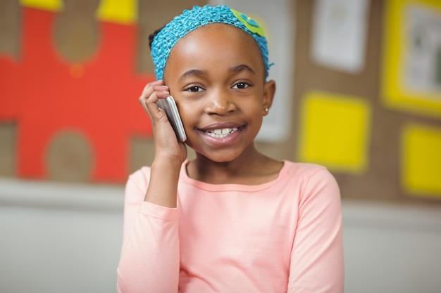 Allievo sveglio che telefona con lo smartphone in un'aula