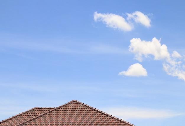 Alloggi il tetto, il cielo blu e la nuvola marroni del mattone.