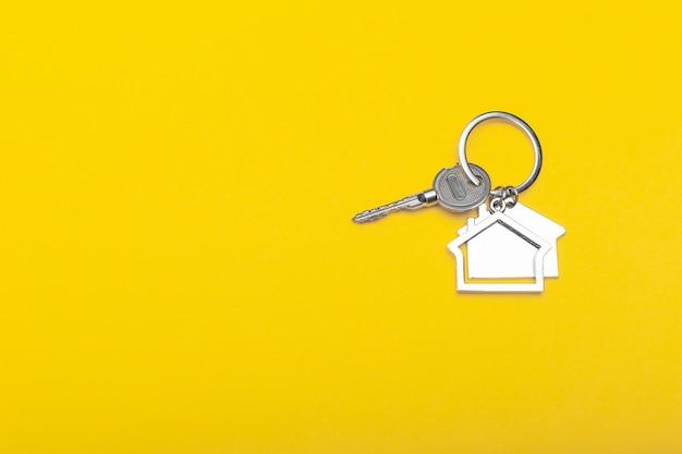 Alloggi le chiavi con il ninnolo sul fondo di colore, vista superiore con lo spazio della copia. chiave di casa su sfondo giallo. stile minimal laico piatto con posto per il testo.