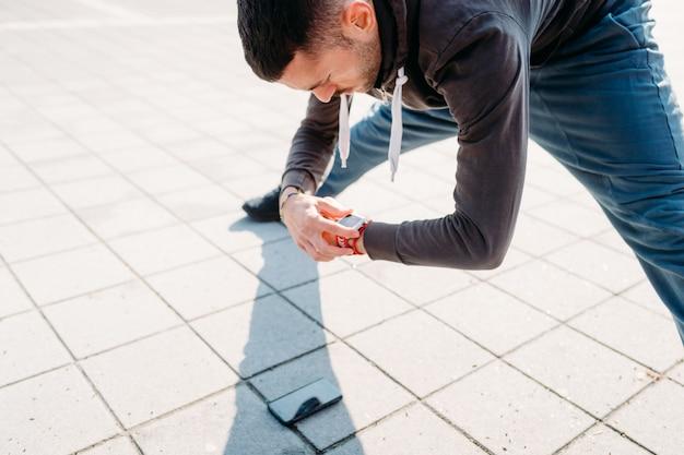 Allungamento all'aperto del giovane facendo uso di smartwatch