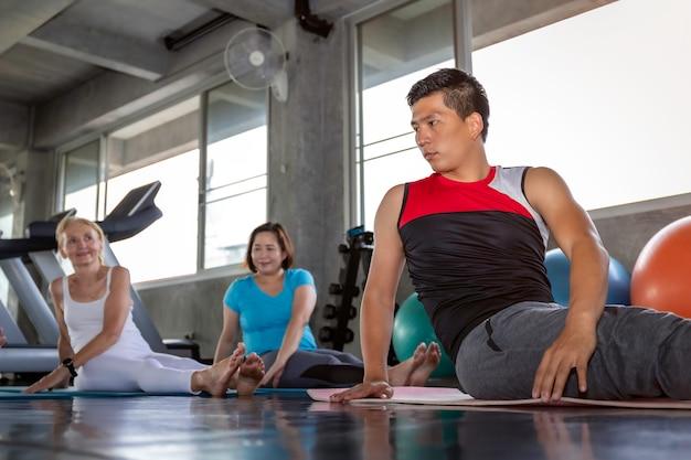 Allungamento attraente del gruppo senior alla palestra di forma fisica.