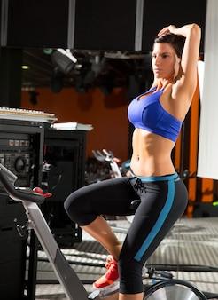 Allungamento della donna dell'allenatore del monitor di filatura di aerobica