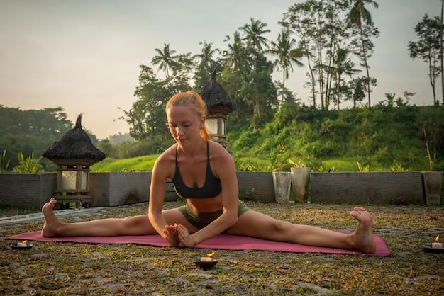 Allungamento di yoga della giovane donna