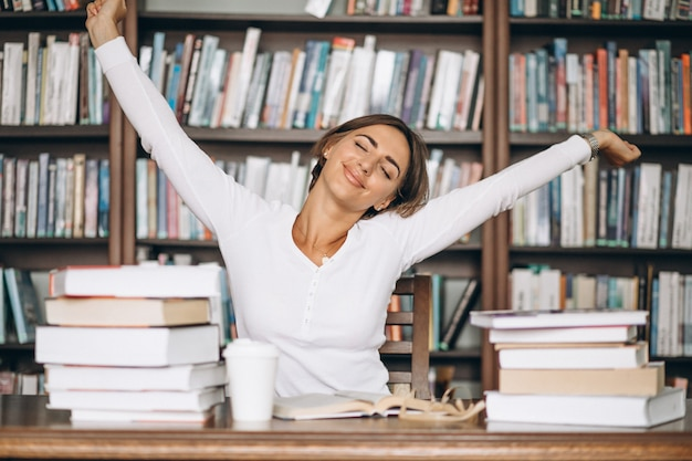 Allungamento stanco della donna alla biblioteca