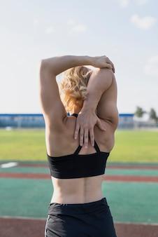 Allungando esercizio con le mani allo stadio