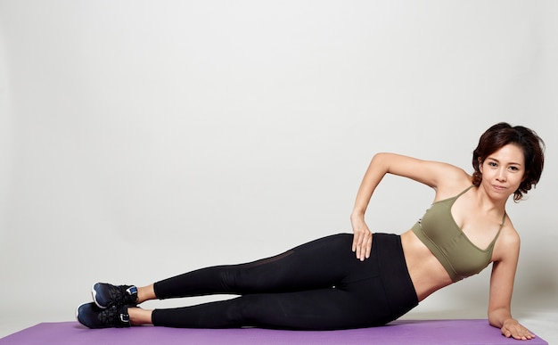 Allungando la postura di allenamento di una donna asiatica su sfondo grigio studio
