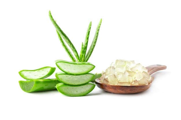 Aloe fresca vera con la fetta e gel nell'isolato del cucchiaio su bianco